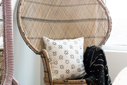 A detail of a wicker peacock chair with a black and white pillow and throw.