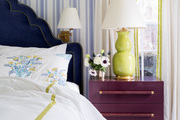 Ceramic bedside lamps, handmade by Christopher Spitzmiller, stand on midcentury-style side tables from Chelsea Textiles.