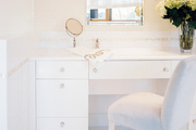 A white vanity with a pair of sconces