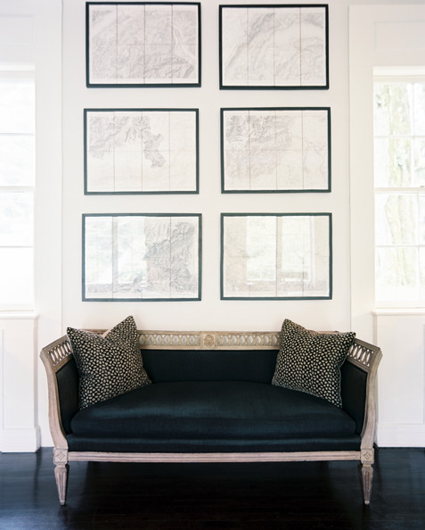 Wall Art - A black settee below a series of framed maps