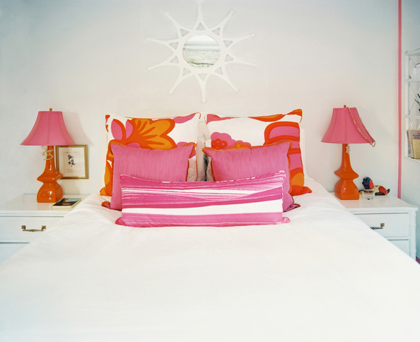 bed pillows a white bedroom with orange and pink lamps and pillows