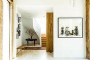 An entryway's curved staircase, wood beams, framed art, and area rug