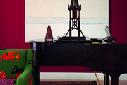 An armchair and a piano against a red accent wall with artwork