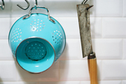 A blue colander and a cleaver hung against white subway tile
