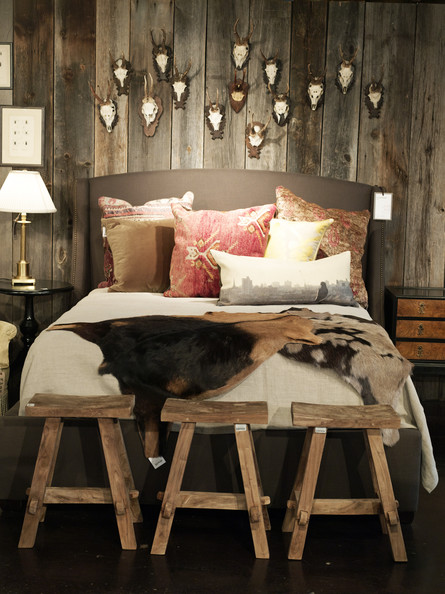 Wood Paneling - A grouping of antlers hung above an upholstered bed