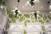 Green palm-frond wallpaper with a grouping of chandeliers