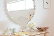 A Scandinavian vanity with an oversized round mirror.