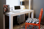 A white Parsons desk paired with a red fretwork chair with zebra-print upholstery