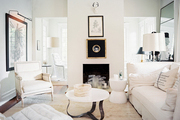 Framed art and white upholstered furniture in a neutral living room