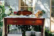 Glassware, dinner plates, and appetizers on an outdoor buffet
