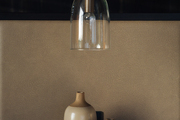 Small glass hanging lamp above square black table.