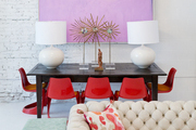 A chandelier and artwork above a dining table with red midcentury dining chairs and a chesterfield sofa