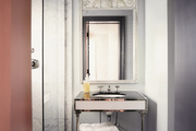 A gray bathroom with an X-base stool and a white sconce
