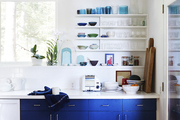 A kitchen with open shelving and blue accents