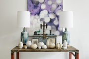 A light fixture above a vintage table with table lamps and ceramics