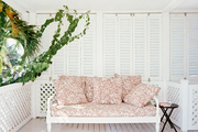 A daybed with patterned cushions on a porch