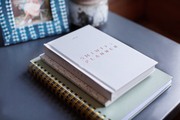 A planner and notebooks on a side table.