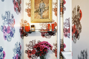 A framed portrait in a bathroom with floral-print wallpaper