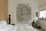 A neutral master bedroom with a storage wall and a painting by Christopher Wool