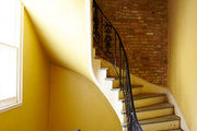 A sunny yellow coats the curving stairway of a Creole townhouse in New Orleans