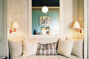 Red wall sconces flanking a daybed and a black coffee table
