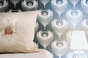 Blue-and-white peacock-feather wallpaper in a bedroom
