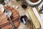 A pizza board, pizza slicer, and place settings for a rustic pizza party