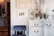 Artworks layered above a white sideboard
