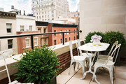Potted boxwoods and white outdoor furniture on a patio with views of Manhattan