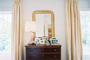 A wooden chest with framed photos and a gold mirror between beige curtains
