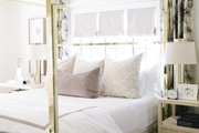 Here is a neutral four-poster bed in the home, backlight by an open window.