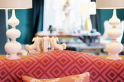 A pair of white lamps behind a pink patterned camelback couch