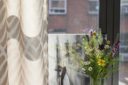 A vase of wild flowers beside an abstract painting and a silver vessel on a window sill