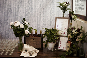 Floral arrangements and drinks atop wooden table