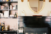 Black lacquered built-in bookcases and a mantel with a pair of shaded sconces