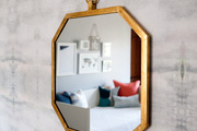 Gold framed octagon mirror hanging on patterned wall.