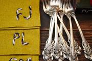 Custom napkins and vintage silverware atop a stained wood dresser.