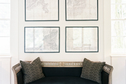 A black settee below a series of framed maps