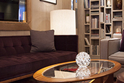 A patchwork rug and a tufted sofa in the midcentury modern library of Belgraves Hotel