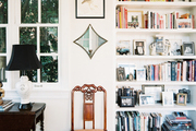 A drop-leaf table and a wooden chair next to built-in bookshelves