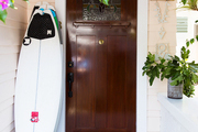 A surfboard beside a front door