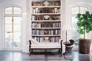 An upholstered bench in front of a built-in bookcase