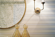 Horizontal stripes accented with a round antiqued mirror and a brass sconce