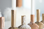 Copper and gold candle holders atop gloss white table.