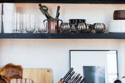 A kitchen counter and shelves stocked with tools and servingware