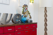An antique foo dog and vintage letters on a red console near a floor lamp
