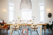 Mix-and-match dining chairs below an oversize chandelier