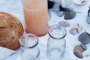 Enamelware and vintage glass bottles on the beach.