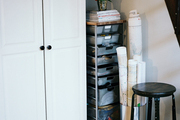 A metal storage rack and a wood-topped stool beside a white cabinet