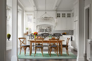Wooden dining table in all white traditional kitchen.